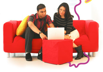 Two people on a red couch looking at a laptop
