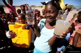 Girl holding glasses of filtered and unfiltered water