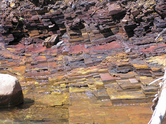 <strong>Layered rocks near Chisholm</strong><br />These thin layers of rock near Chisholm contain various types of iron. Combined with oxygen and hydrogen in different arrangements, each type has its own color.