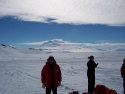 "Pat Hamilton's group, in Antarctica: Hamilton says: ""This is me and part of my group of 20 fellow students out on the Ross Ice Shelf with Mt. Erebus (an active volcano) steaming in the distance.  It was a beautiful day out on the ice with calm winds, clear skies, and a temperature near 40 degrees F.  But weather changes quickly and by the time that we were cooking dinner, it was snowing and windy."""