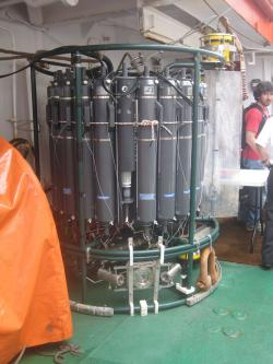 "CTD: As this oceanographic instrument is lowered over the side of a ship, each gray Niskin ""bottle"" can be electronically triggered to collect a seawater sample from a different ocean depth."