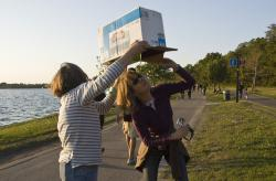 Viewing the eclipse: Two spectators use a an old printer box with a pinhole punched in it to watch the event.