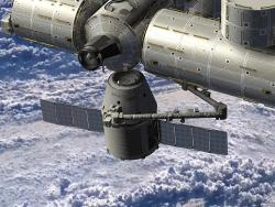 This is not real: But it will be. This is an artist's rendering of the Dragon spacecraft delivering cargo to the ISS. (Dragon is the little winged cylinder and truncated cone.)