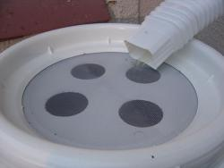 Rain barrel (top detail): Rain barrels like this one collect rain so you can use it to water your garden later. The screens keep children, pets, and mosquitos out, while letting water in. (Photo by chrisdigo)