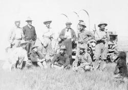Camp Carnegie in Wyoming in 1899: Arthur Coggeshall, sitting far right and donning suspenders, poses for a photograph taken near the Carnegie museum's Sheep Creek quarry in Wyoming. Crews from the American Museum of Natural History and the Carnegie Museum met on the High Plains during the quarrying of Diplodocus carnegii. Standing, left to right: W. D. Mathew, R. S. Lull, H. F. Osborn, W. J. Holland, (unknown on wagon - possibly Willie Reed), Jacob Wortman (with pipe), W. H. Reed. Sitting left to right: Walter Granger, George Mellor, Ira Schallenberger, and  Coggeshall.