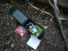 Geocache: Typical geocache and contents.  Photo courtesy Skinny Mike, Flickr Creative Commons.