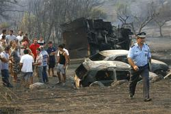 Fire damage: Authorities check through a heavily fire-damaged area of Greece. Hugh wildfires have swept through the southern portions of the country and officials belief they've been deliberately set.