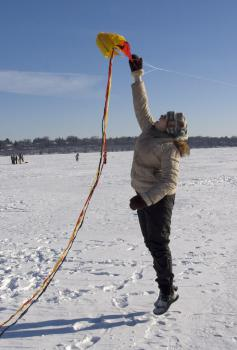 Off we go!!: A bundled kite-flyer gives her aircraft a good boost at launch