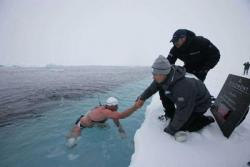 Brrrrrrr: Lewis Gordon Pugh gets help getting back into a boat near the North Pole after his 19-minute swim in 29-degree waters. He made the swim to bring attention to global warming and climate change. (Photo from www.investecnorthpolechallenge.com)