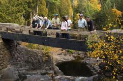 At the Deeps: Geologist Charlie Matsch (center in green cap) explains the geological events that formed the natural popular swimming hole seen in the background.