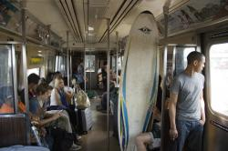 """A"" Train surfer, New York City, 2010: I'm not sure where the surfer dude was going to beat the heat (maybe Long Beach) but the rest of us were headed for JFK to fly away, hopefully, to cooler weather."